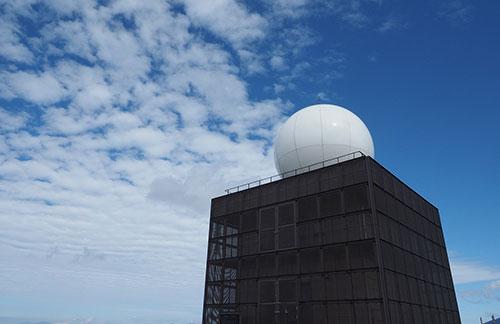 青空の下に黒い四角い建物がありその上に白いドームが乗っている