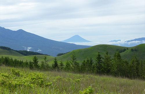なだらかな丘と山の稜線の先に富士山が見える
