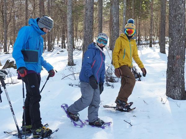 雪上をスノーシューで歩く親子